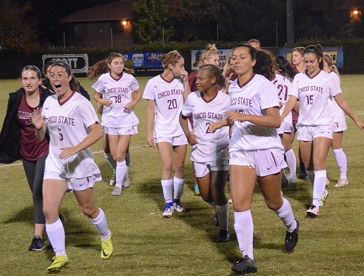 The women's soccer team charges off the field following a win. Photo credit: Jordan Jarrell