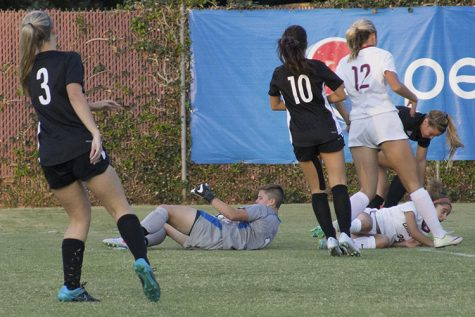 First-year goalkeeper Caityln Duval struggles to get up after being knocked down with first-year forward Sarah Yang. Photo credit: Aubrie Coley