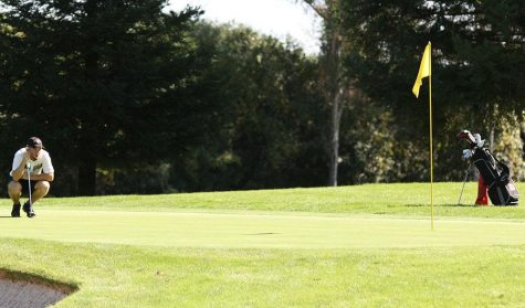 A Chico State golfer examines the green before taking a putt. Photo credit: John Domogma