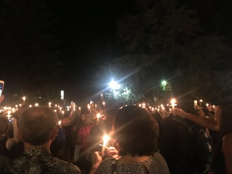 Members of the community gather during the candlelight vigil and raise candles and phones to show their support. Photo credit: Kayla Fitzgerald