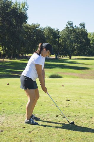 Senior golfer Bianca Armanini tees off during a Wildcat Practice. Orion stock image.