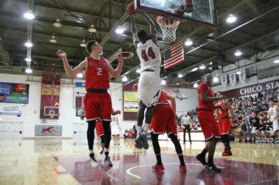 Junior Isaiah Ellis dunks the ball over his opponent in a game. Photo credit: Jacob Auby