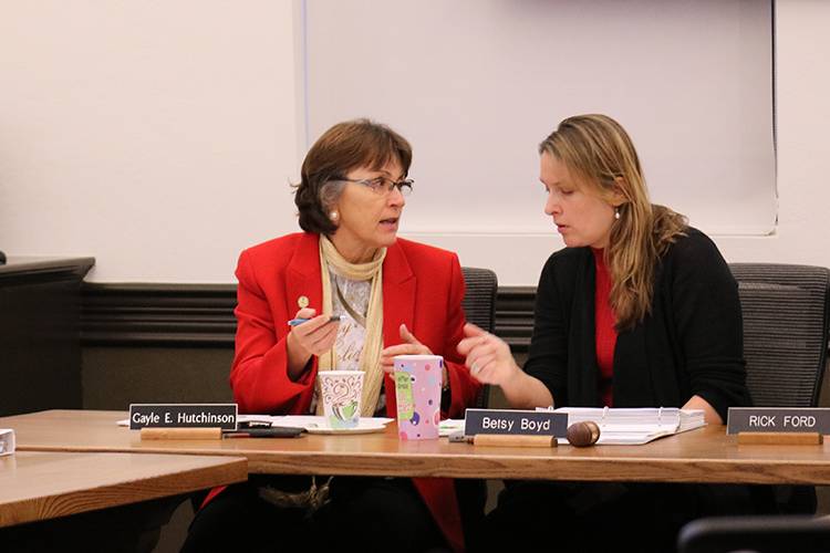 President Gayle Hutchinson speaks with Betsy Boyd at a university budget committee meeting.