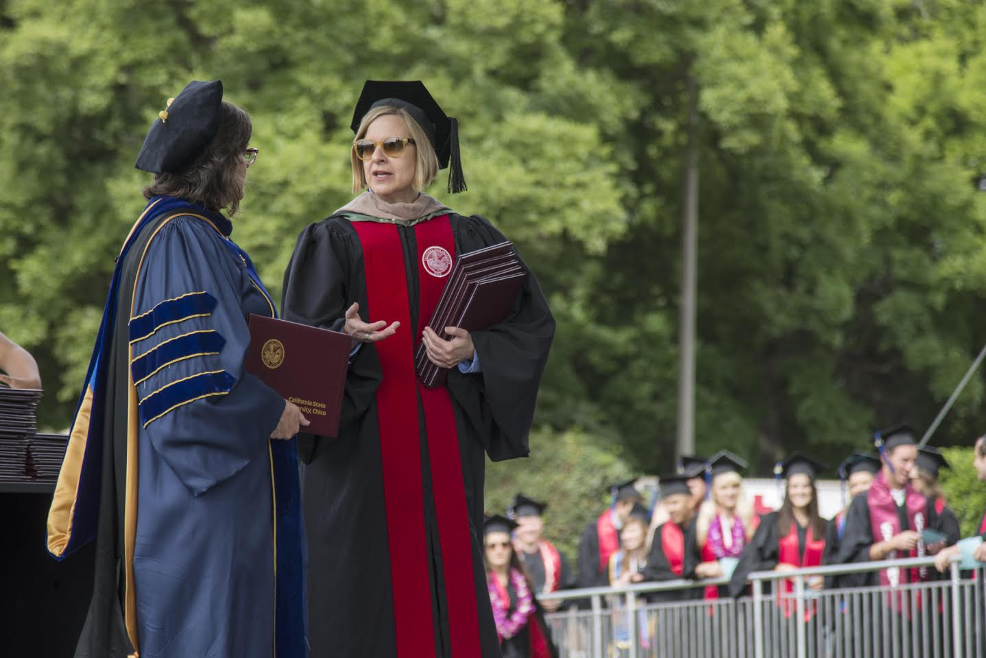 Susan Elrod (left) and Lori Hoffman (right) present diplomas to graduates during the Commencement ceremony for Colleges of Humanities And Fine Arts and Business at University Stadium on Sunday, May 17, 2015 in Chico, Calif.