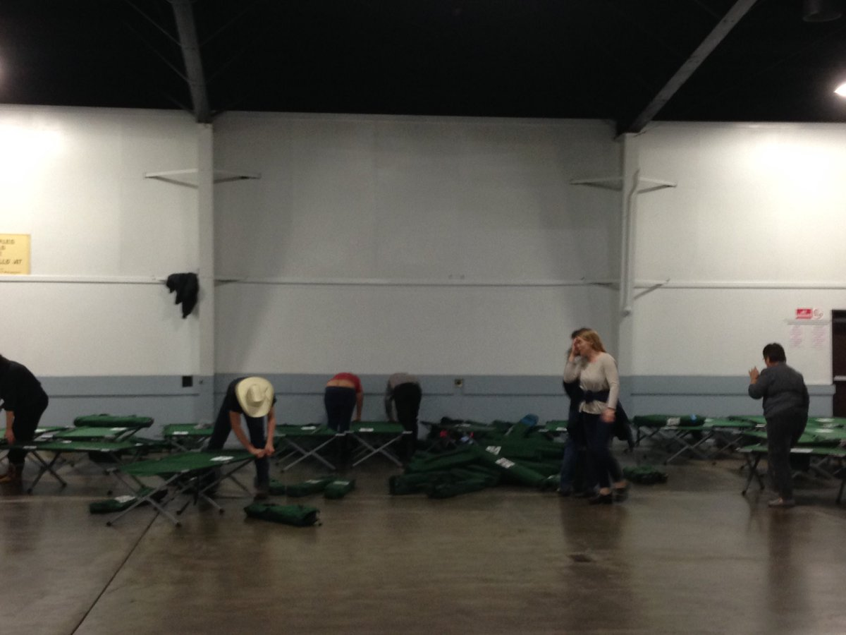 Volunteers set up cots at the Silver Dollar Fairgrounds evacuation center. Photo credit: George Johnston