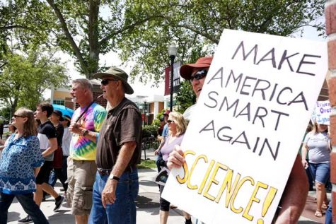 A marcher is seen chanting and holding his sign that reads: Make America Smart Again. Science! Photo credit: Floritzel Salvador