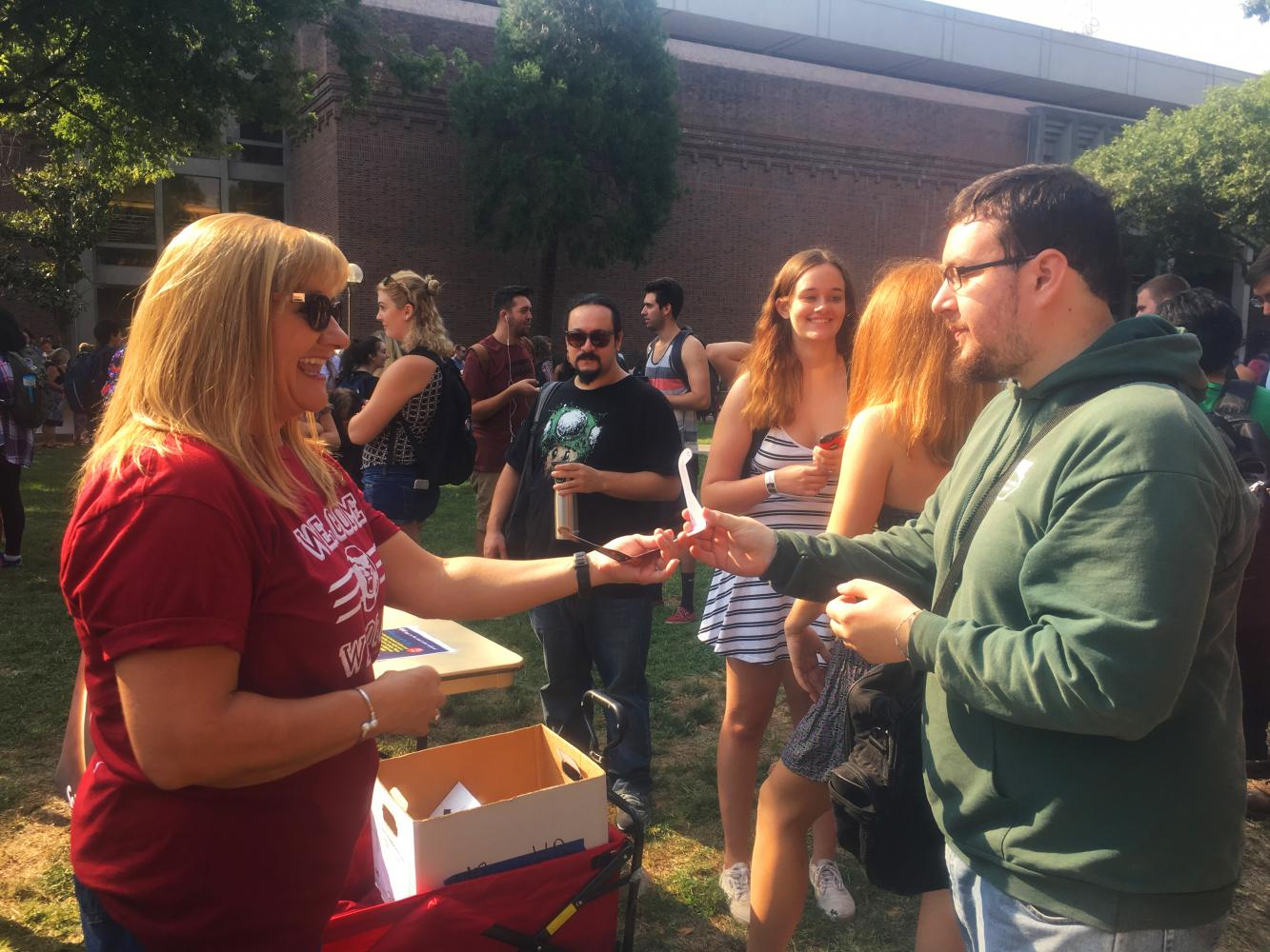 Margie Mitchell hands a student viewing glasses at the Glenn Lawn eclipse viewing party. Photo Credit: Natalie Hanson