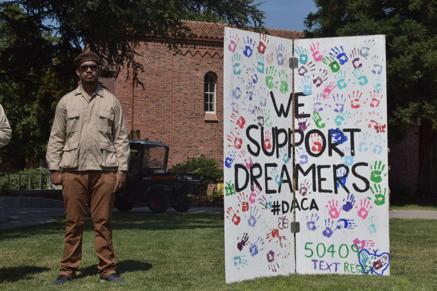 Brown Beret activist stands tall next to student-made banner Photo credit: Nicole Henson