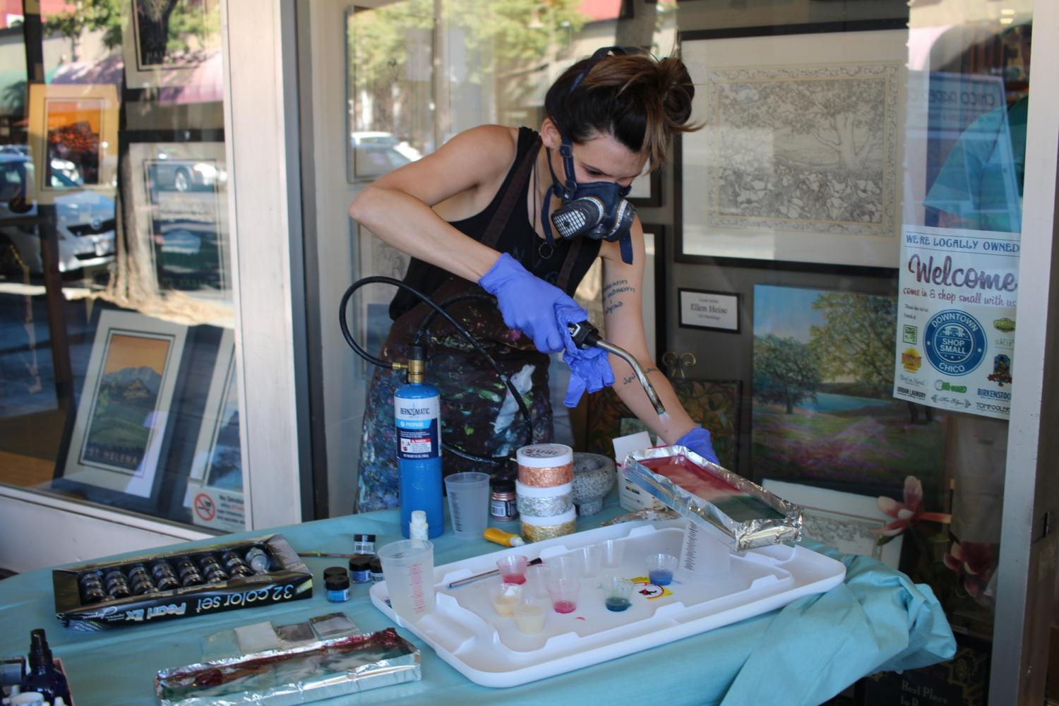 Kathryn Silvera torches the resin. Torching moves the pigments around, as well as popping the bubbles. Photo credit: Sophia Robledo-Borowy