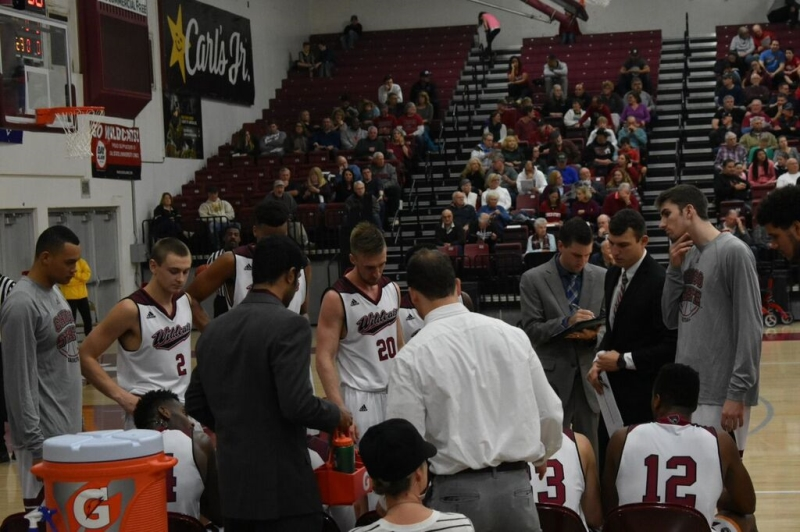 Players listen in as coach Greg Clink leads the huddle of a timeout. Photo credit: Julia Maldonado