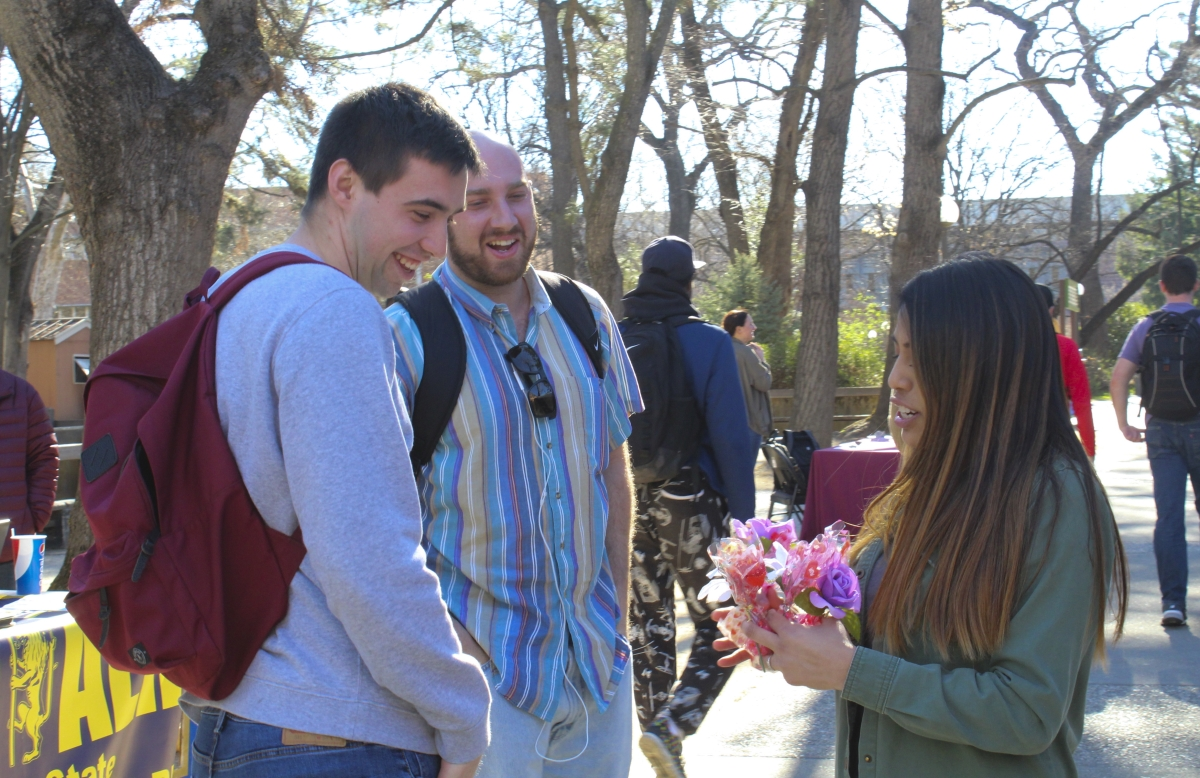 On a sunny February morning, Briana Vazquez of Delta Sigma Pi offers Valentine's Day grams to a couple of curious passerbys on near Plumas Hall. Photo credit: Anne Chamberlain