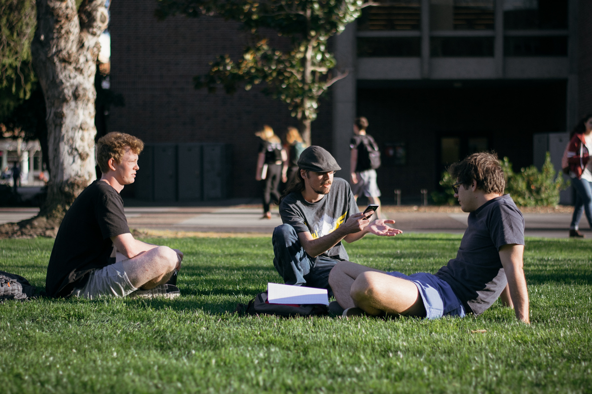 Chico State students, Andrew Freeman, Eric Azevedo, and Jacob Van Meter, take advantage of the warm weather to work on assignments on the Chico State campus. Photo credit: Kate Angeles
