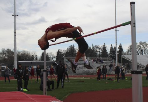 Despite Saturday morning rain, Chico state student athlete & high jump star Tyler Arroyo skillfully wraps his body over pole set at 6 foot 7 inches– a show of raw athletic ability. Photo credit: Anne Chamberlain