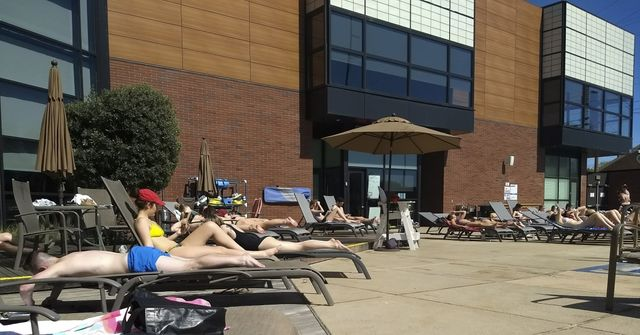 Students crowd in to relax, tan, and study by the Wildcat WREC pool on Tuesday morning. Students are gleeful as a long winter seemingly comes to an end.