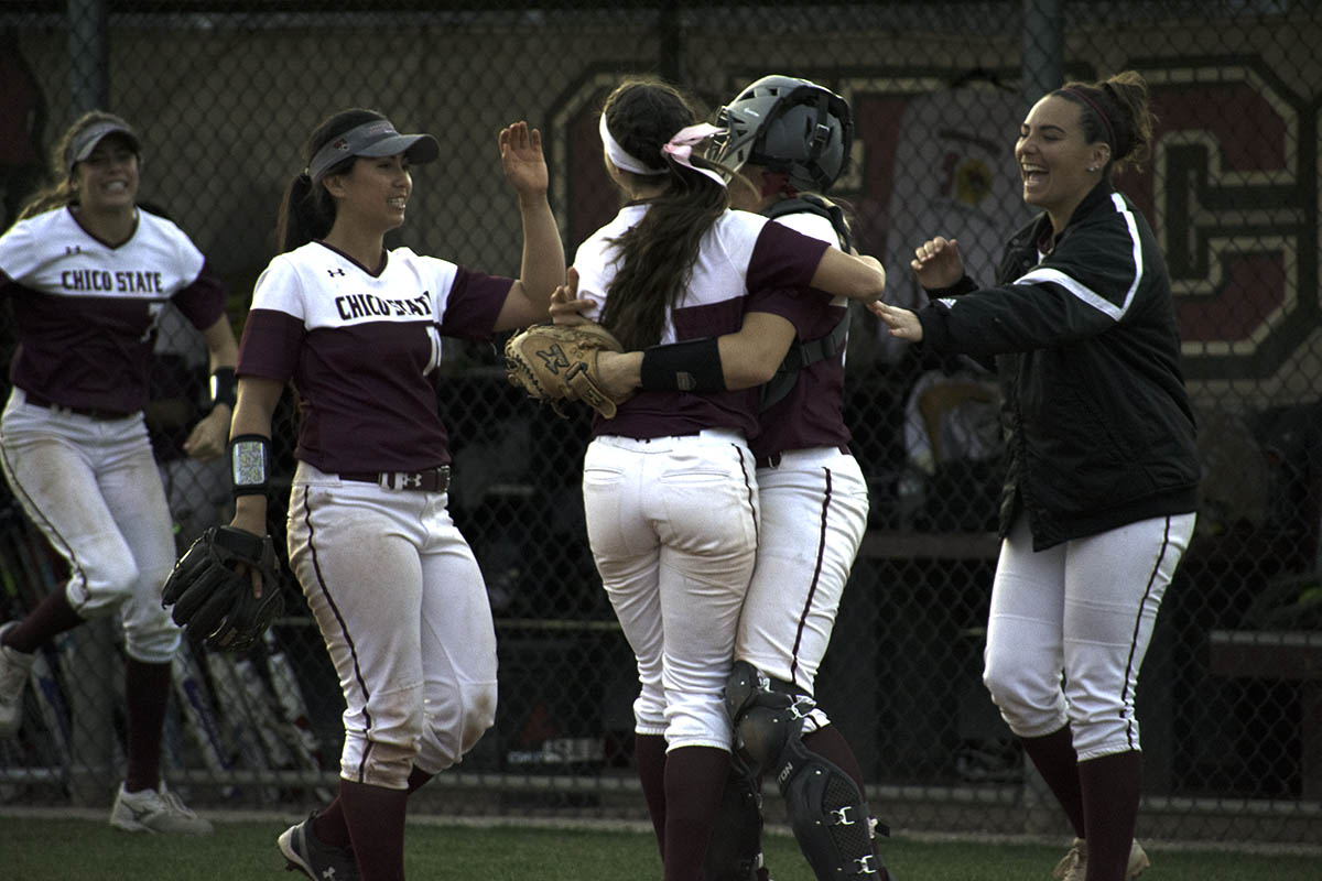 The Wildcats softball team celebrate their second win and pitcher Naomi Monahan's, middle, save.   Celebrating with her is pitcher Haley Gillham, far right, who pitched a no hitter in the earlier game. Photo credit: Martin Chang