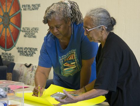 Volunteers Lakshmi and Frances Mann work together to create posters for the Martin Luther King remembrance walk. Photo credit: Carly Maxstone