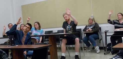 With a unanimous show of hands, the group endorses candidates for a position. Photo credit: Josh Cozine