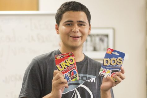 Christopher Hernandez holds up his prizes Sunday after becoming the first winner of the game Lotería at the Second Annual Welcome Week Game Night. Photo credit: Brian Luong