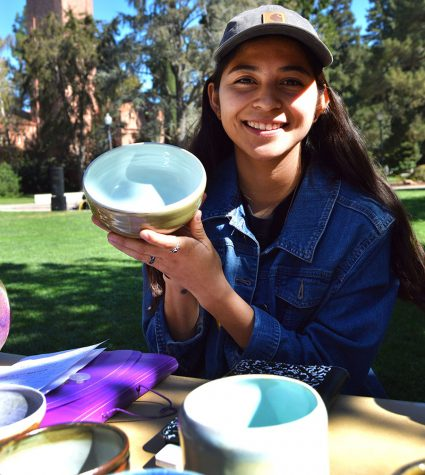 Child Development major Patty DeLeon shows off a ceramic piece she made during the pottery sale in front of Trinity Commons. Photo credit: Olyvia Simpson