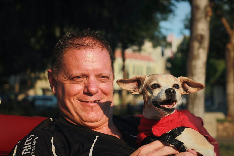 Mike G smiles with his dog while resting on his pedicab. Photo credit: Tara Killoran