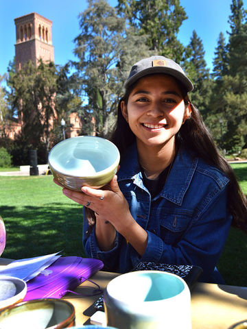 Child Development major Patty DeLeon shows off a ceramic piece she made at Trinity Commons. Photo credit: Olyvia Simpson