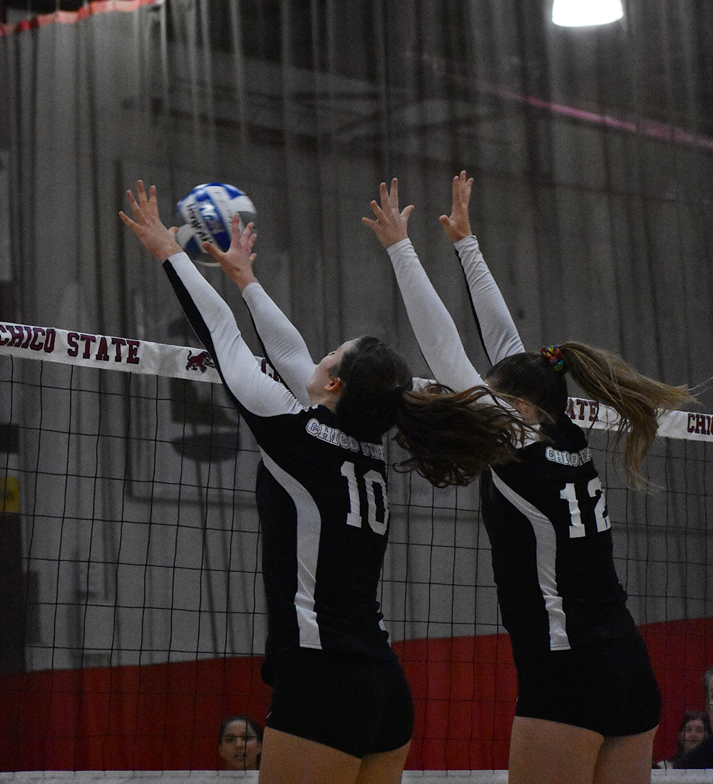Bekah Boyle (left) and Makaela Keeve (right) reach to double block Cal State San Bernardino's right-side hitter. Photo credit: Julia Maldonado