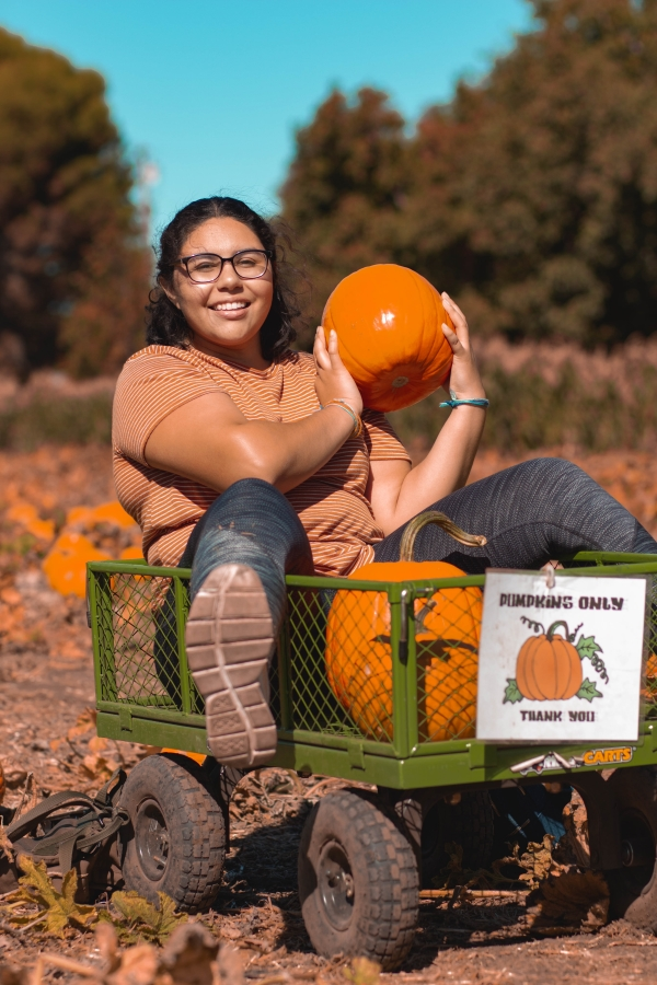 Student Kelly Portillo excited about the pumpkins she got from The Hubs trip to Peterson Sisters Pumpkin Patch. Photo credit: Maury Montalvo