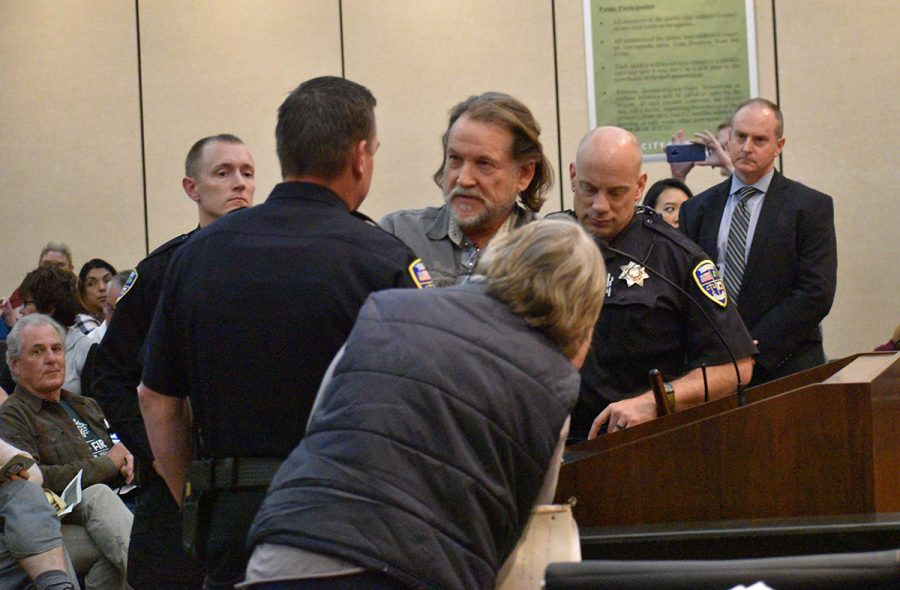 Patrick Newman speaks with police officers at the Chico city council meeting Tuesday. Newman spoke at the podium in front of the city council to oppose the sit and lie ordinance that ended up passing later in the evening. This ordinance allows police officers to detain and remove homeless and transient people that are
