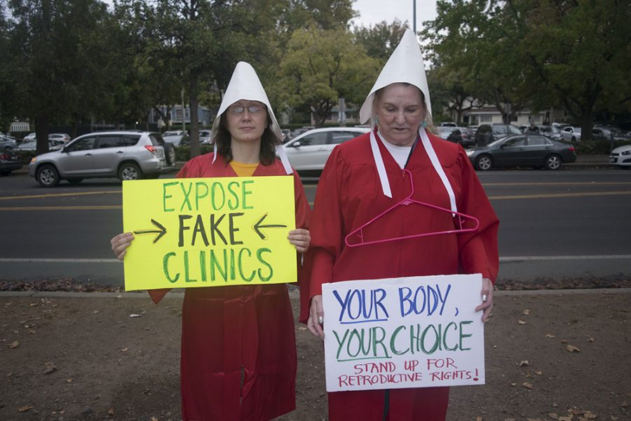 Protestors Mandy Hackney and Nancy Good, dressed as handmaids Friday to protest the Women's Resource Clinic.