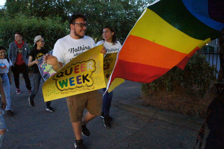 Several Pride Marchers with their queer week posters. Photo credit: Keelie Lewis