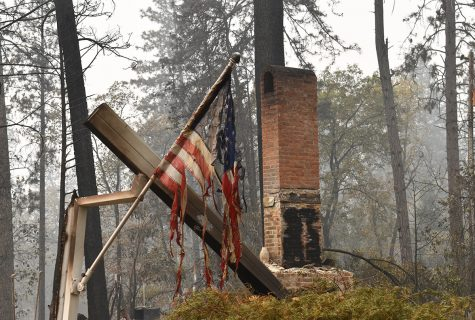 A flame-shredded American flag hangs on a mostly burnt piece of wood on Wildwood Lane in Paradise. Photo Credit: Alex Grant