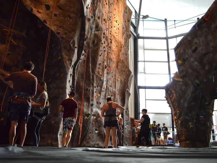 Students get prepared with their harnesses and look at the different rock climbing courses to choose from the one they want to attempt to climb to reach the top. Photo credit: Olyvia Simpson