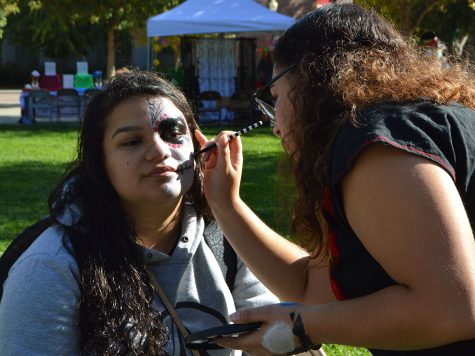 Dellanira Carrillo has half of her face painted like a sugar skull by Saidi Montoya in Trinity Commons on Friday. Check out this story and more on this week's newscast. Photo credit: Olyvia Simpson