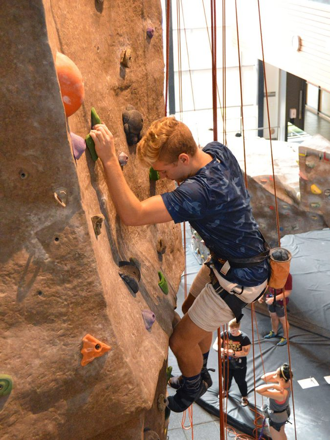 Eli+Urlie+puts+his+rock+climbing+skills+to+the+test+at+The+Shredding+event+on+Sunday+at+the+Wrec+Climbing+Gym.+The+climbing+wall+had+new+top+rope+courses+for+students+to+master.+Photo+credit%3A+Olyvia+Simpson