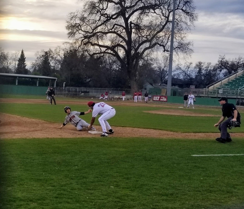 Chico State third baseman Kristian Scott attempts to tag Simpsons' Creed Smith in the fifth inning. Photo credit: Brandon Downs