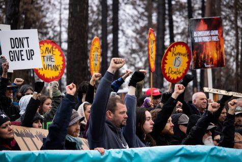 Stephen Murray stands at the center of the banner with Camp Fire survivors raising their fists in unity to symbolize a #ClimateUprising, Sunday, Feb. 17, 2019, in Paradise, CA. Murray lost both his home and job in the blaze. Photo credit: Christian Solis