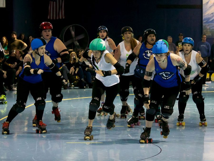 "Jess Jarocki or ""Tripsy McStumble"" races against the Sacramento Flood Water jammer as they both hurry to pass one another to earn more points during the match. Michaella King or ""Rebel Rose"" is the pivot and dictates the pace of the jam match. She gets ready to slam into the Flood Water opponent so Jarocki can pull ahead. Photo credit: Olyvia Simpson"