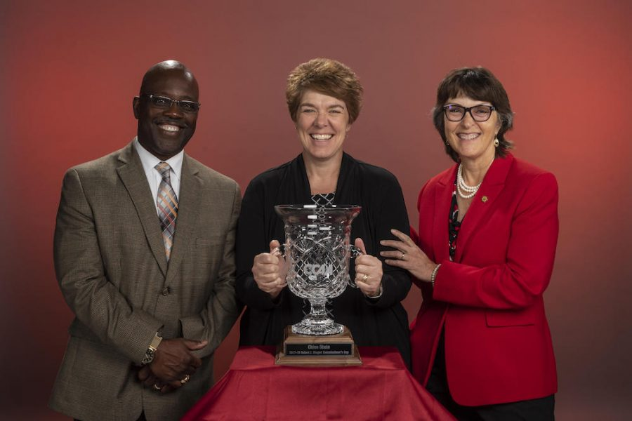 Milton Lang (VPSA), Anita Barker, and President Gayle Hutchinson (right) stand behind the 2017-18 Robert J. Hiegert Commissioner's Cup trophy on Monday, September 24, 2018 in Chico, Calif. The award, named in honor of former long-time Commissioner and CCAA Hall of Famer, Robert J. Hiegert, is given to the California Collegiate Athletic Association (CCAA) member institution with the highest aggregate ranking in eight of the CCAA's 13 championship sports. The Wildcats won five CCAA championships during the year accumulating 99.5 points, helped by championship seasons in men's and women's cross country, men's golf, men's track and field and softball. In addition, Chico State netted extra points in the standings for winning the 2018 CCAA Softball Tournament. (Jason Halley/University Photographer/CSU Chico) Photo credit: Jason Halley - University Photographer