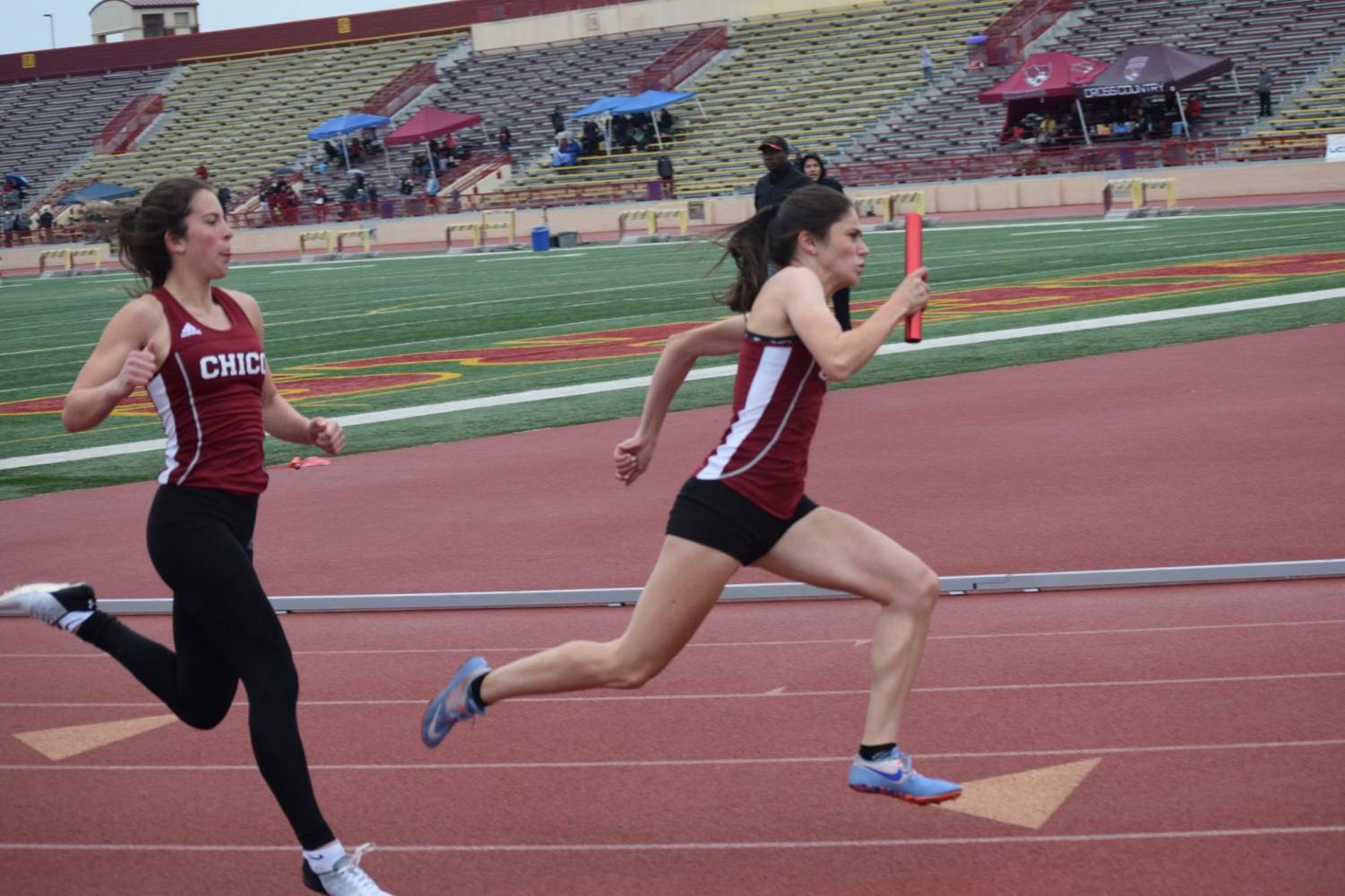 Isabella Moyer passing on the baton to Lyndsey Settle in the invitational track meet Sunday. Image courtesy of Chico State Sports Information.