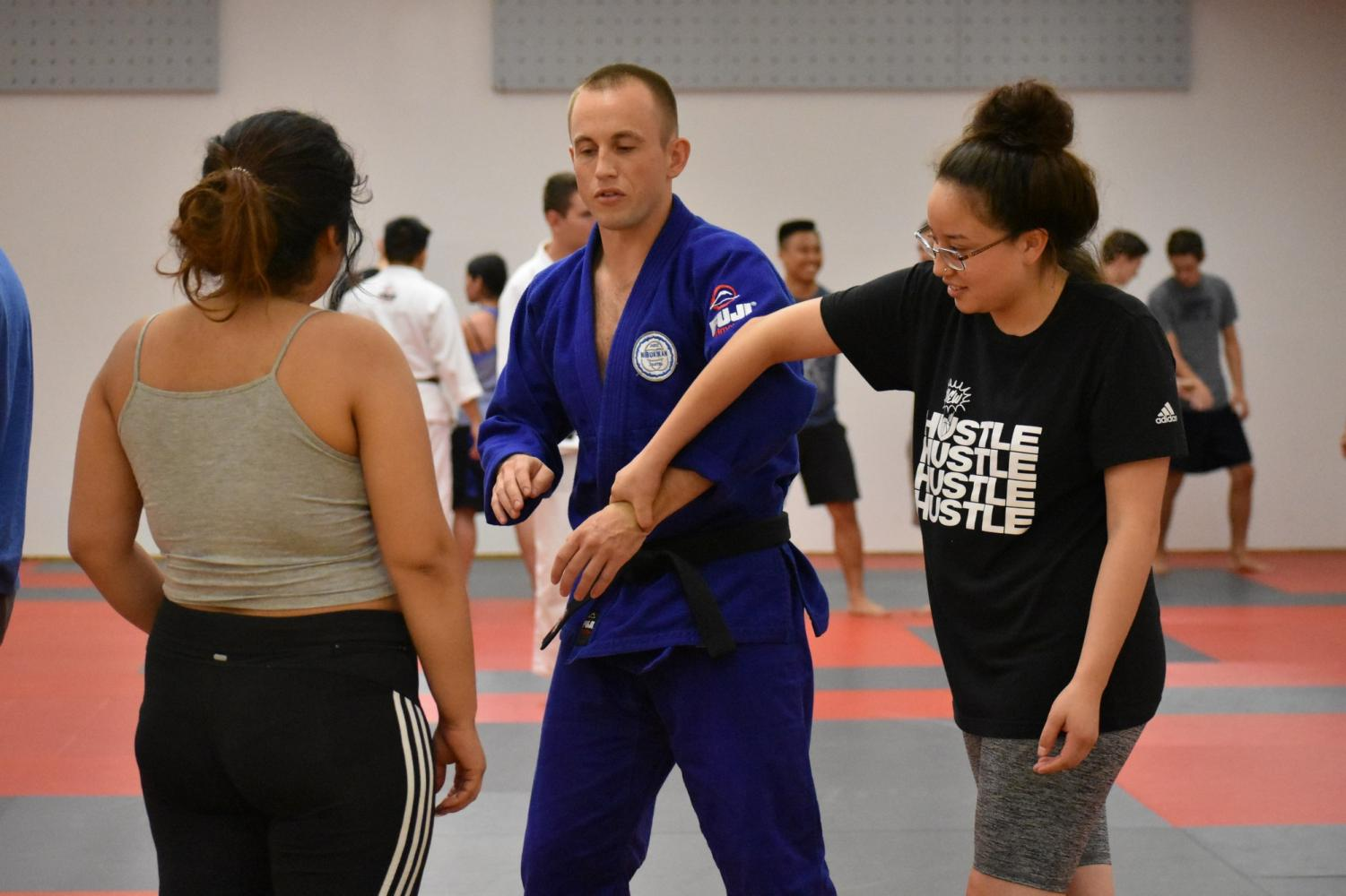Instructor Austin Stahl teaches a breakaway technique to two students. Photo credit: Lucero Del Rayo-Nava