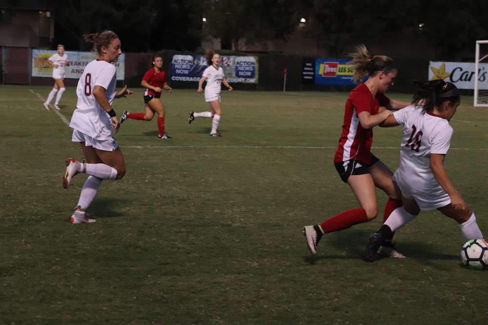 Alexi Vontsolos in defensive battle with Holy Names player. Photo credit: Melissa Herrera