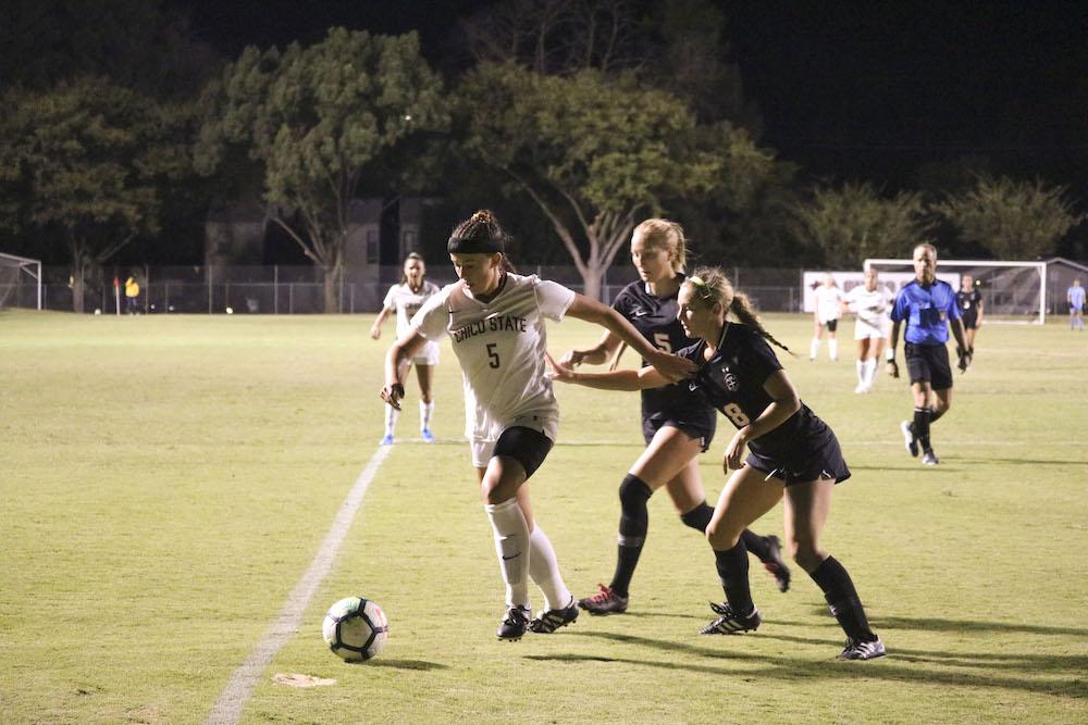 Kyra Greenwood kicks the ball as two Azusa players run after her. Photo credit: Melissa Herrera