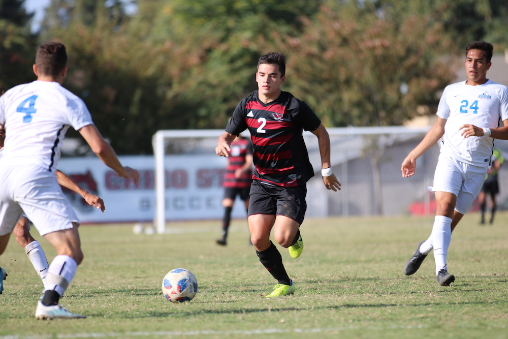 Mikey Hirsch defending the ball not letting Tony Di Donato (far left) and Sergio Gonzales (far right) get the ball. Photo credit: Hana Beaty