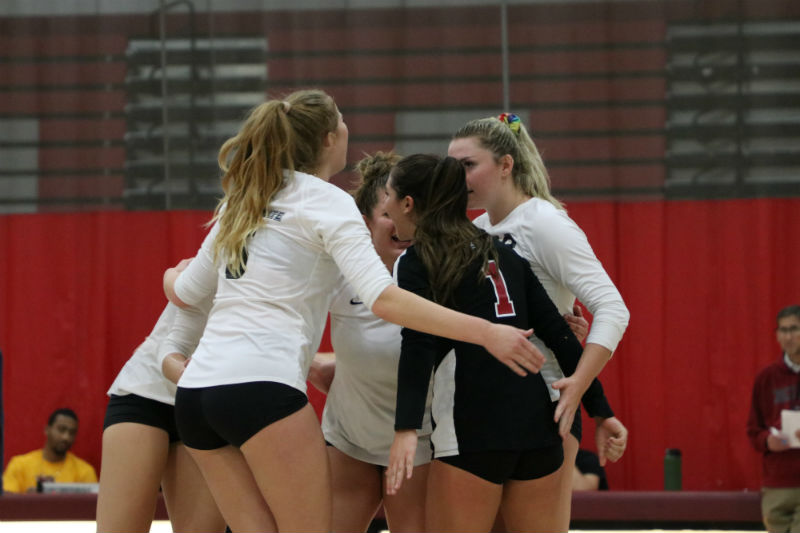 The volleyball team huddles up to strategize about the game. Photo credit: Mary Vogel