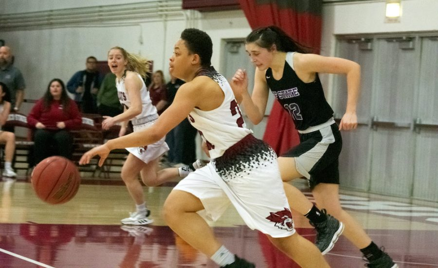 Shay Stark dribbles the ball down the court with a Gator defender trailing.
