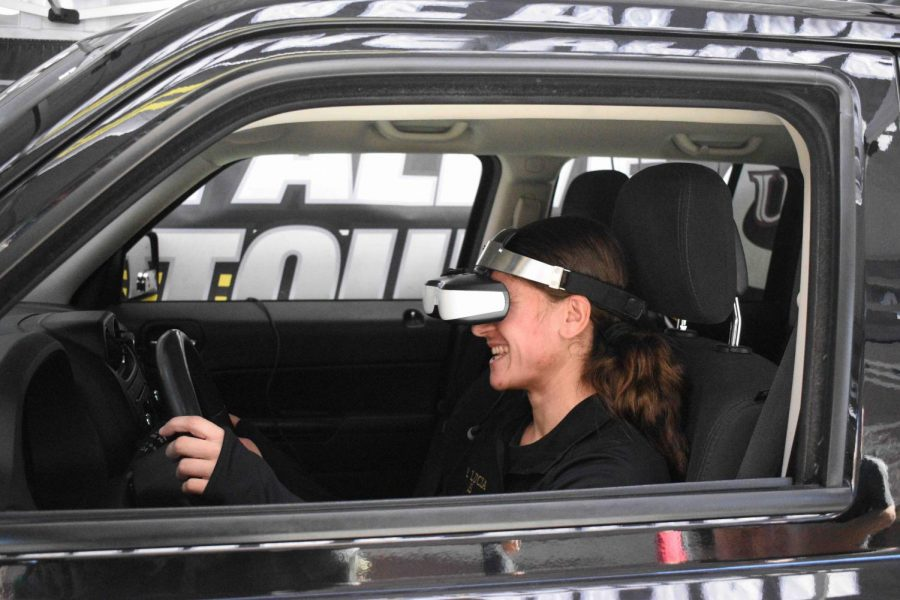 A woman is driving a car simulating drunk driving.