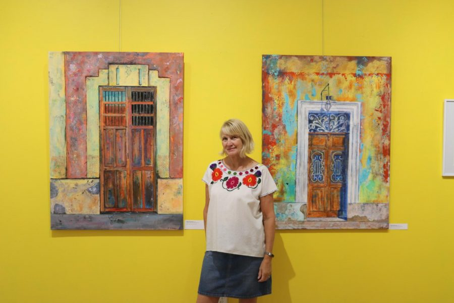 Reta Rickmers posing along side per acrylic paintings inspired by photos she took while in Yucatan, Mexico