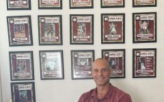 Chico State men's basketball head coach Greg Clink sits in his office in front of pictures of former Wildcats.