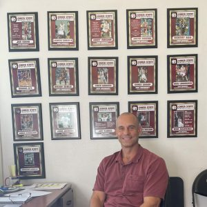 Chico State mens basketball head coach Greg Clink sits in his office in front of pictures of former Wildcats.