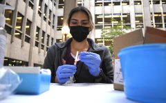 Silvia Bustos prepares a flu vaccine outside of the Meriam Library on Oct. 22